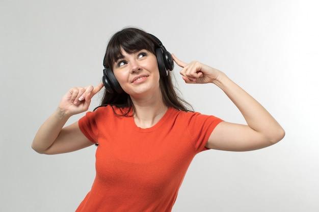 Lachende jonge dame, luisteren naar muziek via oortelefoons in ontworpen t-shirt in goed humeur met lang haar op wit Gratis Foto