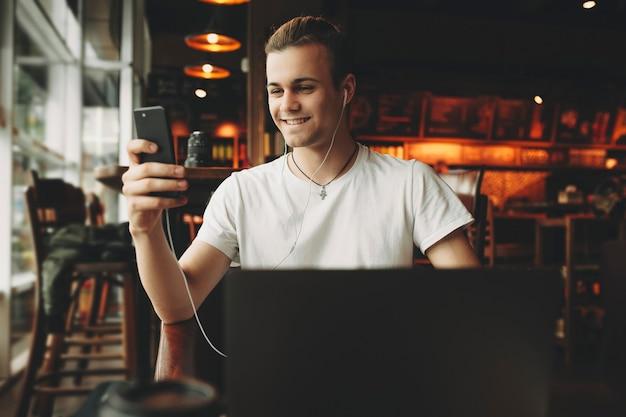 Lachende jonge man in wit overhemd zit op laptop in oortelefoons en kijken naar het scherm van de mobiele telefoon in donkere elegante café Premium Foto