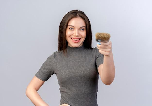 Lachende jonge mooie vrouw verf penseel uitrekken op camera en hand zetten taille geïsoleerd op een witte achtergrond met kopie ruimte Gratis Foto