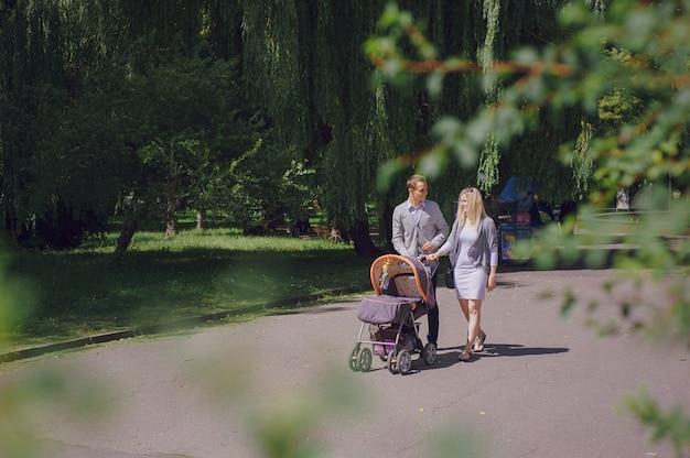 Lachende jonge ouders wandelen met hun baby Gratis Foto