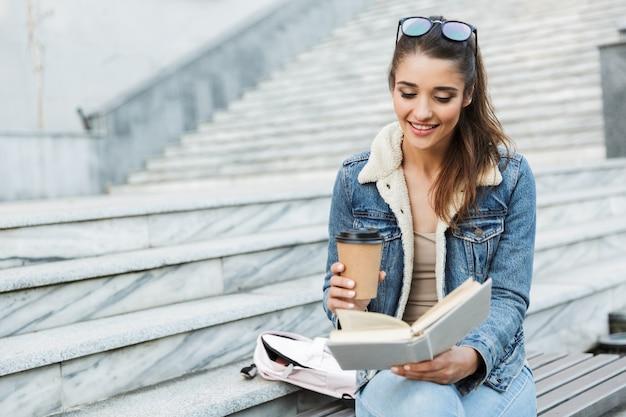 Lachende jonge vrouw draagt jas zittend op een bankje buitenshuis, boek lezen, kopje afhaalmaaltijden koffie te houden Premium Foto