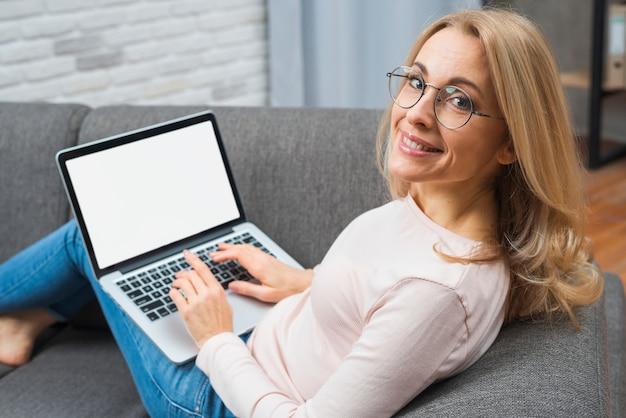 Lachende jonge vrouw zittend op de bank met laptop op haar schoot kijken camera Gratis Foto