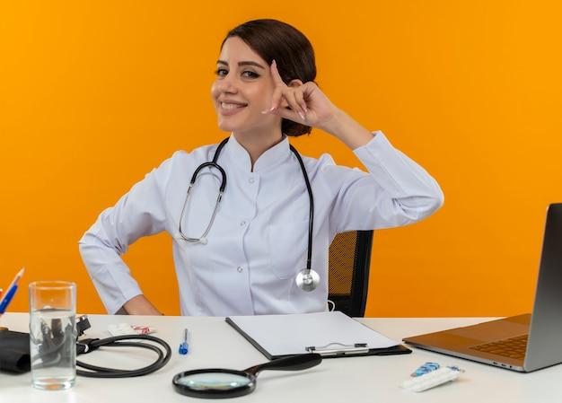 Lachende jonge vrouwelijke arts medische gewaad dragen met stethoscoop zit aan bureau werken op computer met medische hulpmiddelen vinger op voorhoofd op isolatie gele achtergrond Gratis Foto