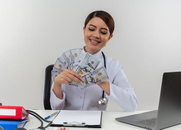 Lachende jonge vrouwelijke arts medische mantel dragen met een stethoscoop zit aan bureau werken op computer met medische hulpmiddelen houden en kijken naar contant geld met kopie ruimte Gratis Foto