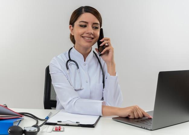 Lachende jonge vrouwelijke arts medische mantel dragen met een stethoscoop zit aan bureau werken op computer met medische hulpmiddelen speake op telefoon en gebruikte laptop met kopie ruimte Gratis Foto