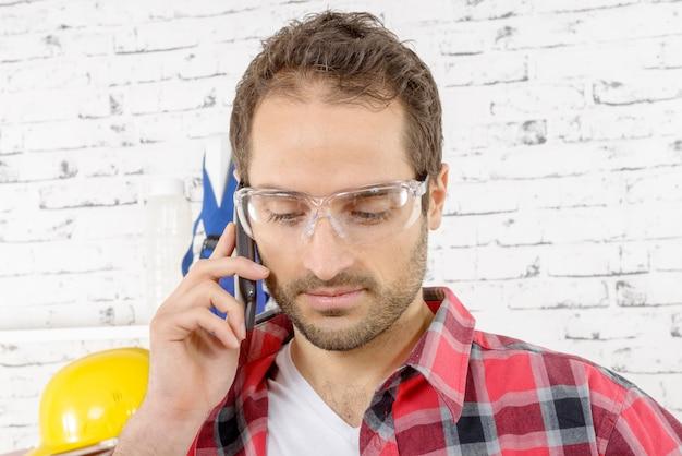 Lachende jonge werknemer telefoons in zijn atelier Premium Foto