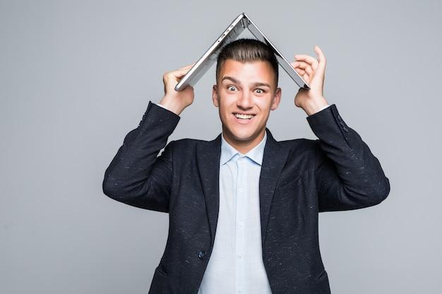 Lachende jongeman poseren met laptop op zijn hoofd gekleed in een donkere jas in studio geïsoleerd op een grijze muur Gratis Foto