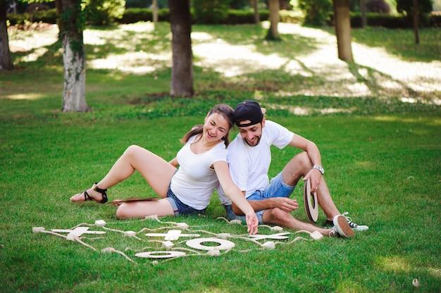 Lachende jongen en meisje die tic-tac-teen in het park spelen Premium Foto