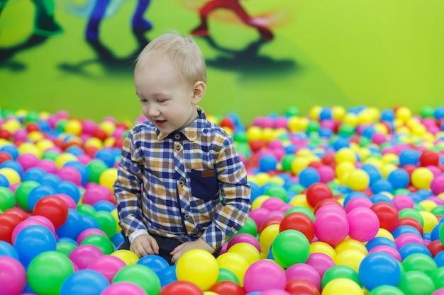 Lachende jongen in zwembad met veelkleurige ballen. familie rust in kindercentrum. het glimlachen van jongen speelt in de speelkamer. gelukkige jeugd. Premium Foto
