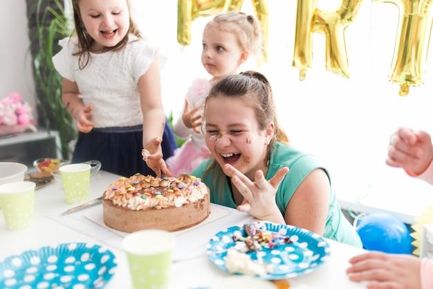 Lachende kinderen en tiener die cake proeven Gratis Foto