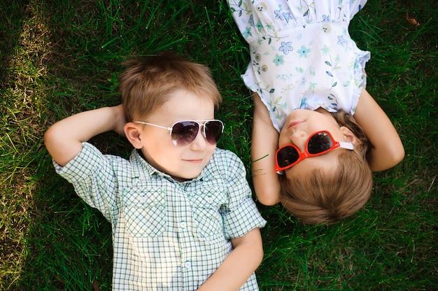 Lachende kinderen in de tuin in zonnebril Premium Foto