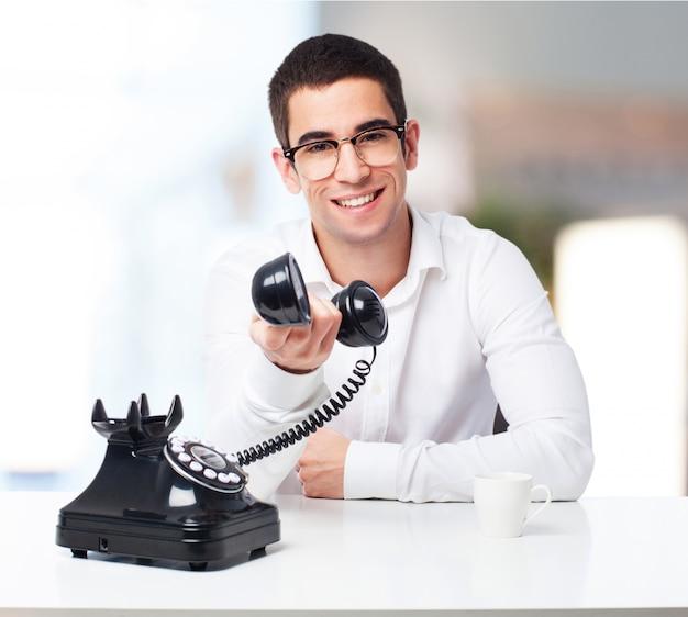 Lachende man met een antieke telefoon in zijn hand Gratis Foto