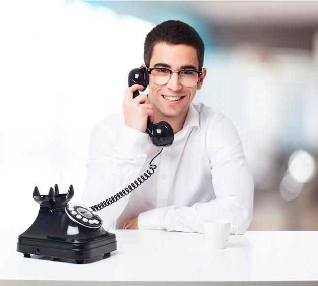 Lachende man te praten op een zwarte telefoon Gratis Foto
