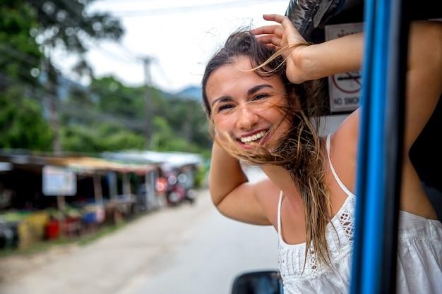 Lachende meisje kijkt uit het raam van een taxi, tuk-tuk Gratis Foto
