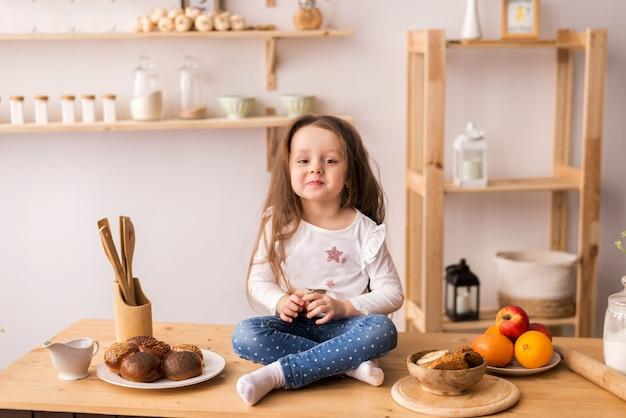 Lachende meisje, zittend op het werkoppervlak van de keuken te wachten voor het ontbijt. vrolijk en ondeugend meisje in de keuken. Premium Foto