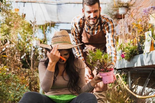 Lachende mensen met potplant Gratis Foto