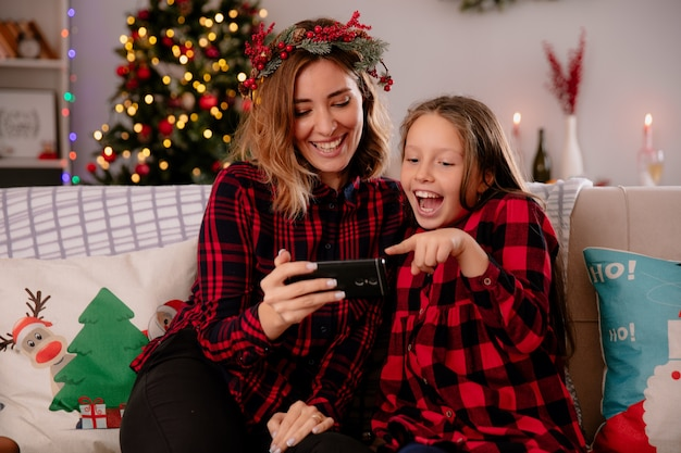Lachende moeder en dochter kijken naar iets op telefoon zittend op de bank en genieten van kersttijd thuis Gratis Foto