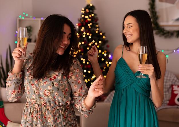 Lachende mooie jonge meisjes houden glazen champagne genieten van kersttijd thuis Gratis Foto