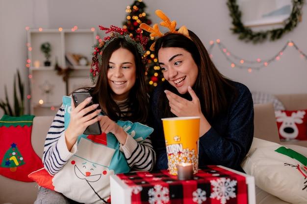 Lachende mooie jonge meisjes met hulstkrans en rendieren hoofdband kijken naar telefoon zittend op fauteuils en genieten van kersttijd thuis Gratis Foto
