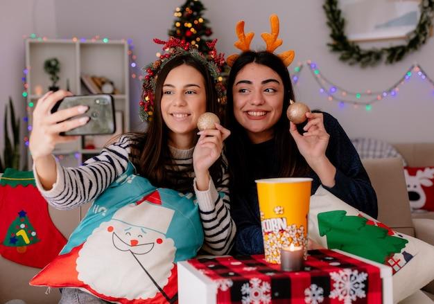Lachende mooie jonge meisjes met hulstkrans en rendierhoofdband houden glazen bol ornamenten vast en nemen selfie zittend op fauteuils en genieten van kersttijd thuis Gratis Foto