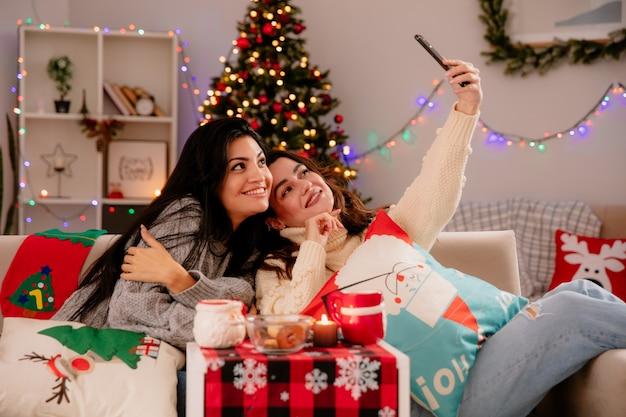 Lachende mooie jonge meisjes nemen selfie zittend op fauteuils en genieten van kersttijd thuis Gratis Foto