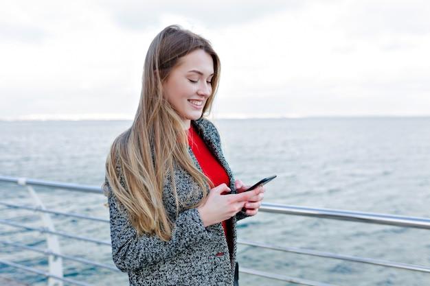 Lachende schattige vrouw in grijze jas en rood shirt scrollende smartphone aan de kade en geniet van mooi weer Gratis Foto