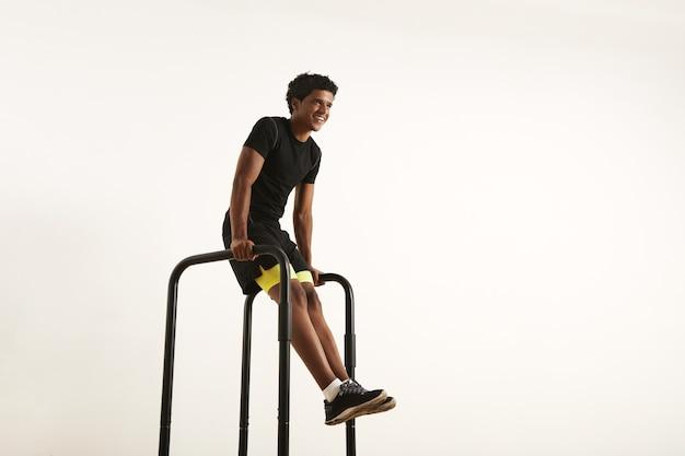 Lachende sterke afro-amerikaanse atleet met een afro, gekleed in zwart synthetisch shirt en zwarte en gele korte broek doet l-zit op korte balken thuis geïsoleerd op wit. Gratis Foto