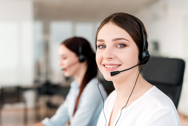 Lachende technische ondersteuning agent met headset beantwoorden van zakelijke oproepen in het kantoor van het bedrijf Premium Foto