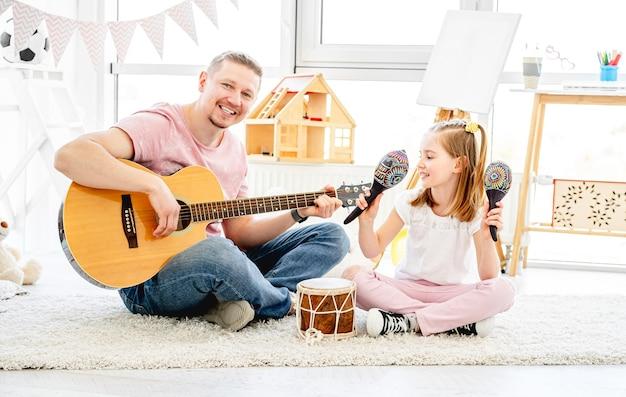 Lachende vader en dochtertje spelende muziekinstrumenten in de kinderkamer Premium Foto