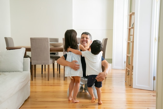 Lachende vader knuffelen schattige kleine kinderen thuis Gratis Foto