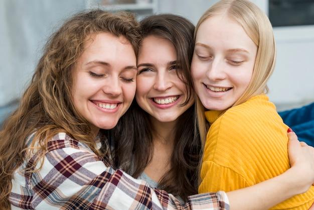 Lachende vrienden knuffelen Gratis Foto