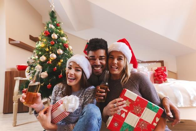 Lachende vrienden poseren met geschenken en flessen bier in handen in de slaapkamer. kerst vakantie concept. Premium Foto