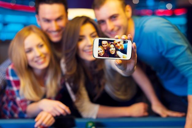 Lachende vrienden selfie foto nemen van nachtclub met biljart Gratis Foto