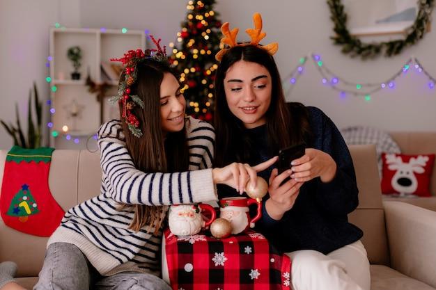 Lachende vrij jonge meisjes met holly krans en rendieren hoofdband kijken naar telefoon zittend op fauteuils en genieten van kersttijd thuis Gratis Foto