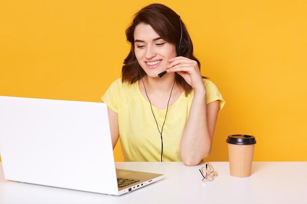 Lachende vrolijke ondersteuning telefoon operator vrouw in hoofdtelefoon heeft een gesprek met haar cliënt, geïsoleerd op geel Premium Foto