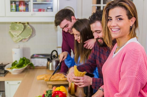 Lachende vrouw die bij de camera glimlacht die en maaltijden bij lijst spreekt met vriendenhoogtepunt van groenten en deegwaren voorbereidt Premium Foto
