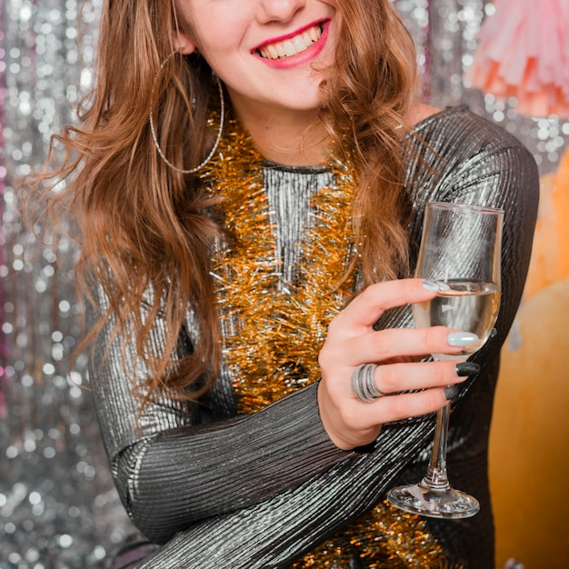 Lachende vrouw in avondjurk met een glas drank Gratis Foto