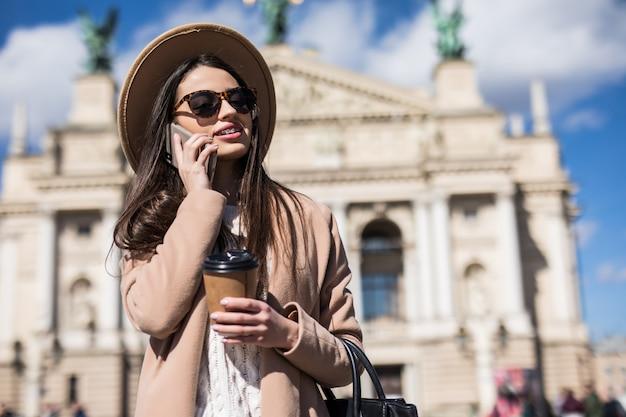 Lachende vrouw in casual herfst kleding praten aan de telefoon Gratis Foto