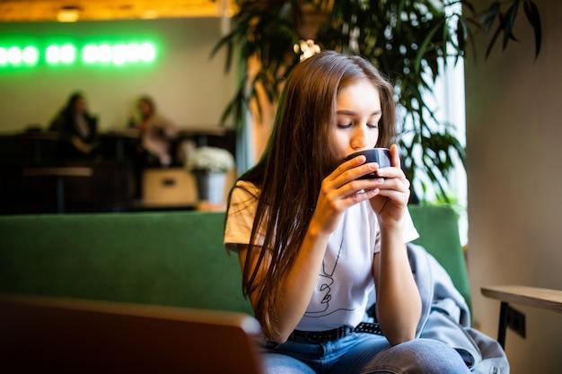 Lachende vrouw in een goed humeur met een kopje koffie zitten in café. Gratis Foto