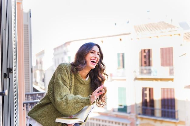 Lachende vrouw met boek Gratis Foto