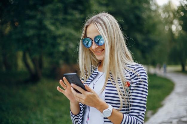 Lachende vrouw met een zonnebril te typen op een mobiel Gratis Foto