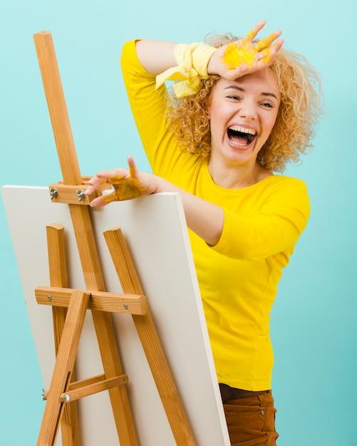Lachende vrouw met gele verf Gratis Foto