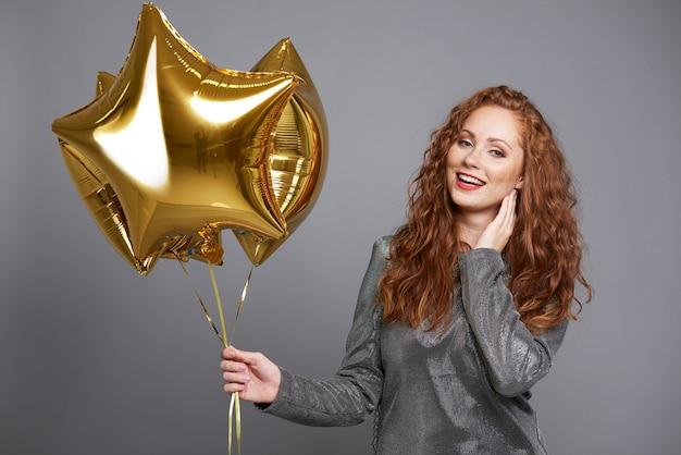 Lachende vrouw met stervormige ballonnen Gratis Foto