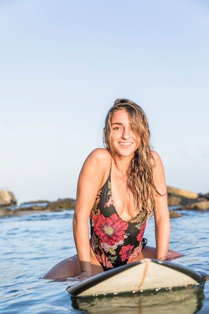 Lachende vrouw zittend op een surfplank Gratis Foto