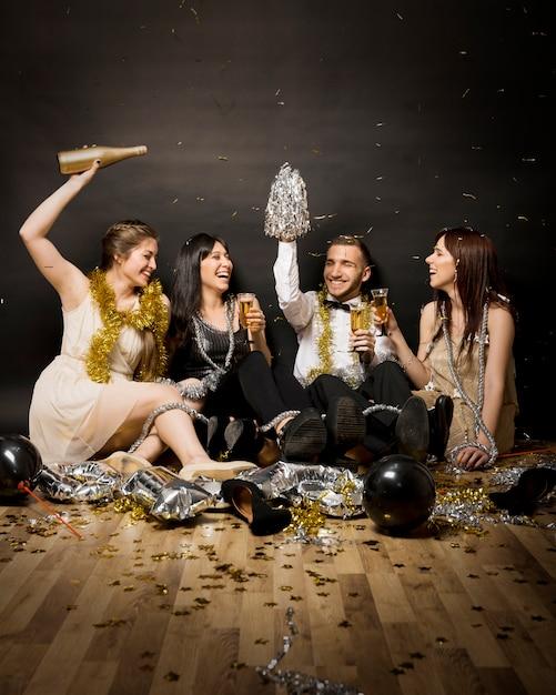 Lachende vrouwen en man in avondkleding met glazen dranken op vloer Gratis Foto