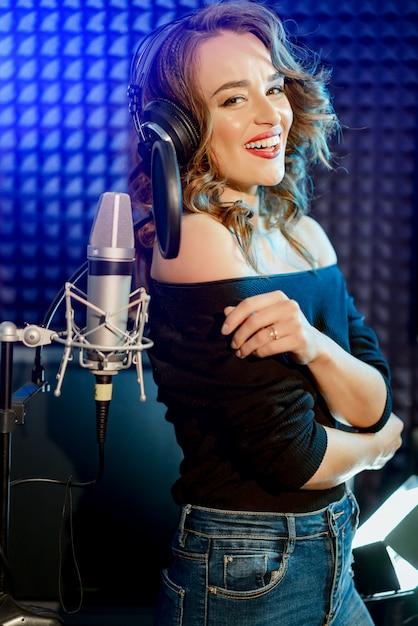 Lachende vrouwenzanger met hoofdtelefoons dichtbij de microfoon met een uitdrukking van geluk Premium Foto