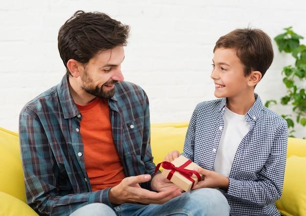 Lachende zoon biedt een geschenk aan zijn vader Gratis Foto