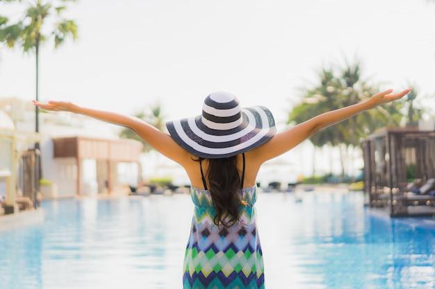 Lacht de gelukkige jonge glimlach van de portret mooie jonge aziatische vrouw en rond zwembad in hoteltoevlucht Gratis Foto