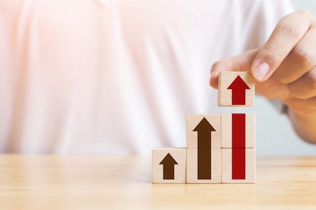 Ladder carrière pad voor zakelijke groei succes proces concept. hand schikken hout blok stapelen als opstapje met pijl omhoog Premium Foto