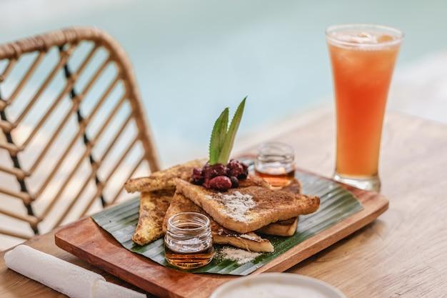 Lade met voedsel en koekjes op een houten tafel naast een glas sap en koffie Gratis Foto